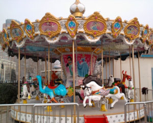 Riding Kiddie Carousels At The Amusement Park