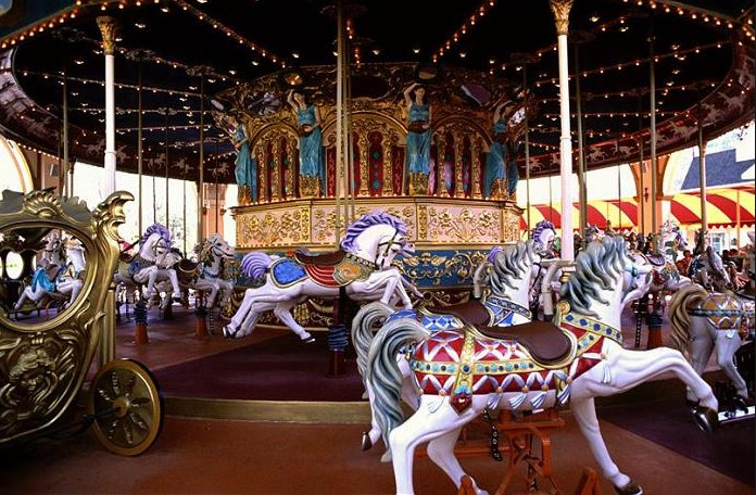 Riding On A Vintage Carousel Or A Fiberglass Carousel